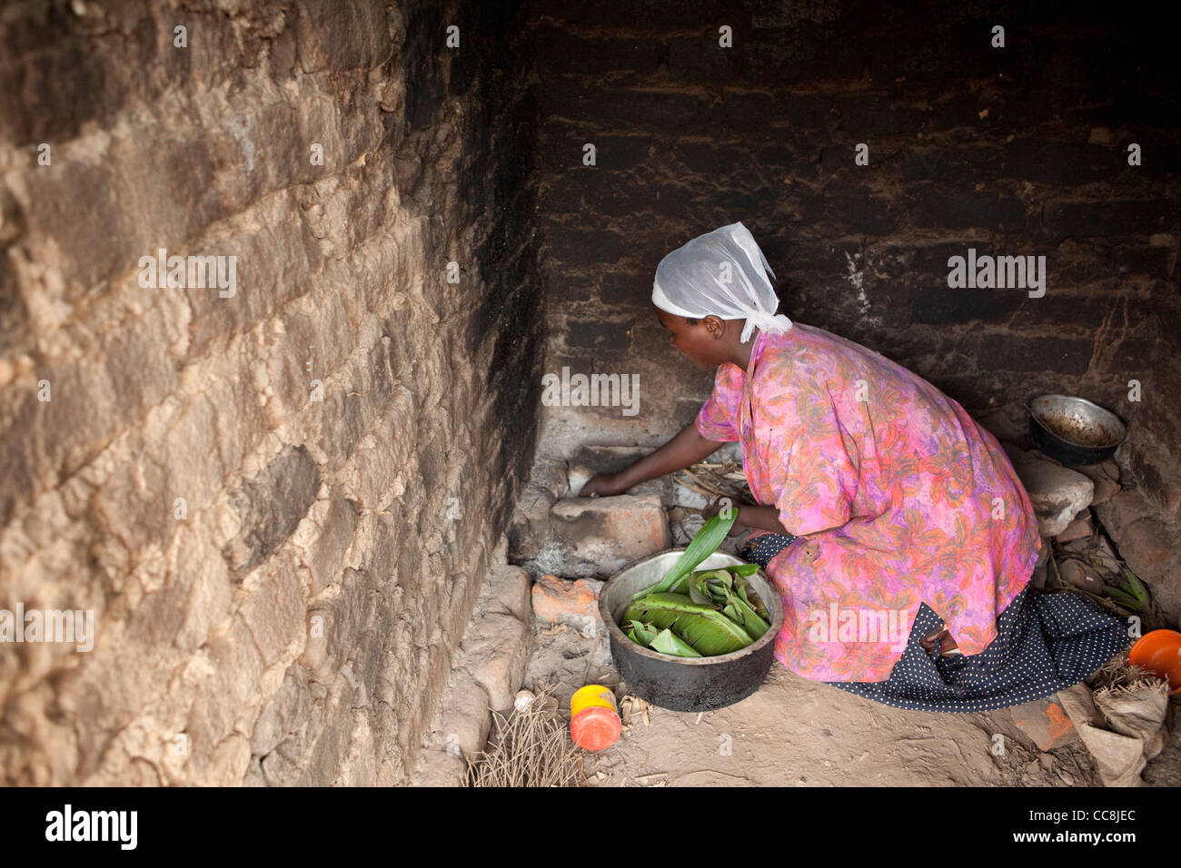 A woman cooks over an open stove in Masaka, Uganda, East Africa - Stock Image