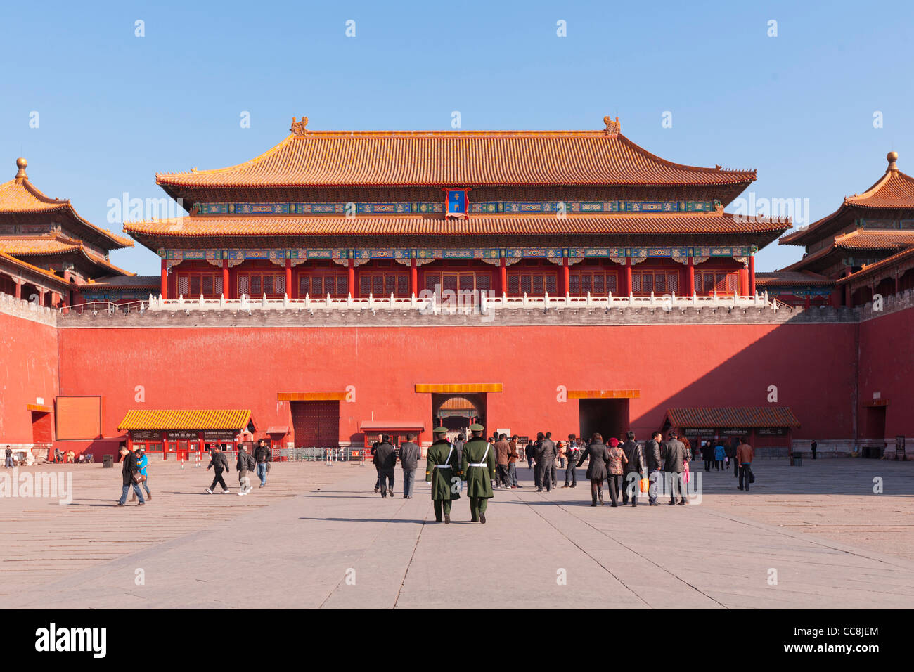 Tourists and police guards in the courtyard in front of the Meridian Gate, in the Forbidden City in Beijing. - Stock Image