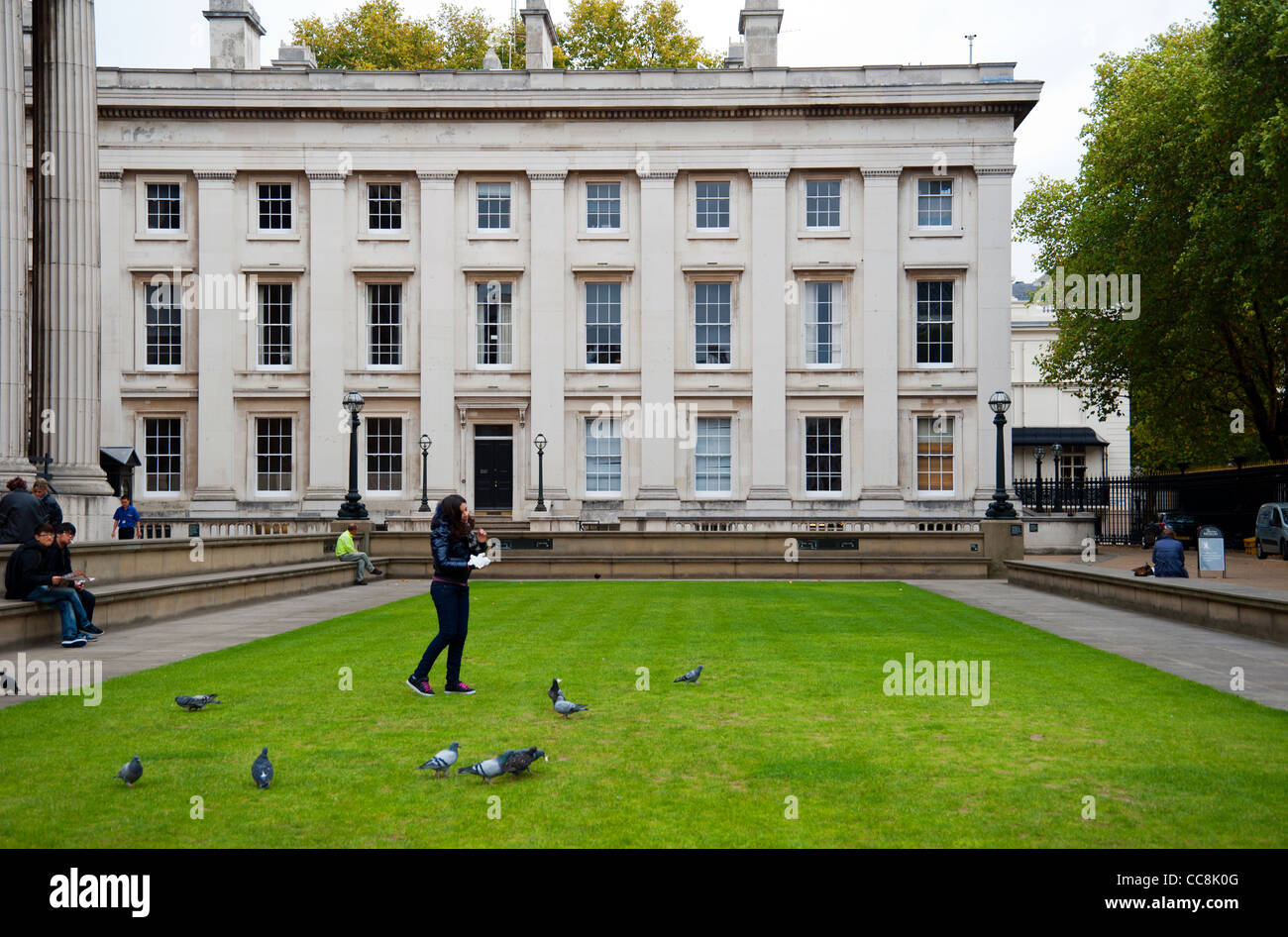 Feeding pigeons on the lawn outside the British Museum, London, UK - Stock Image