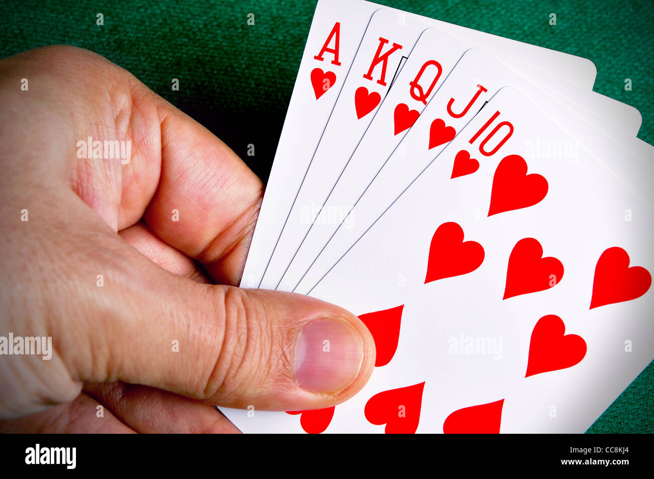 Hand holding a Royal Flush poker card sequence - Stock Image