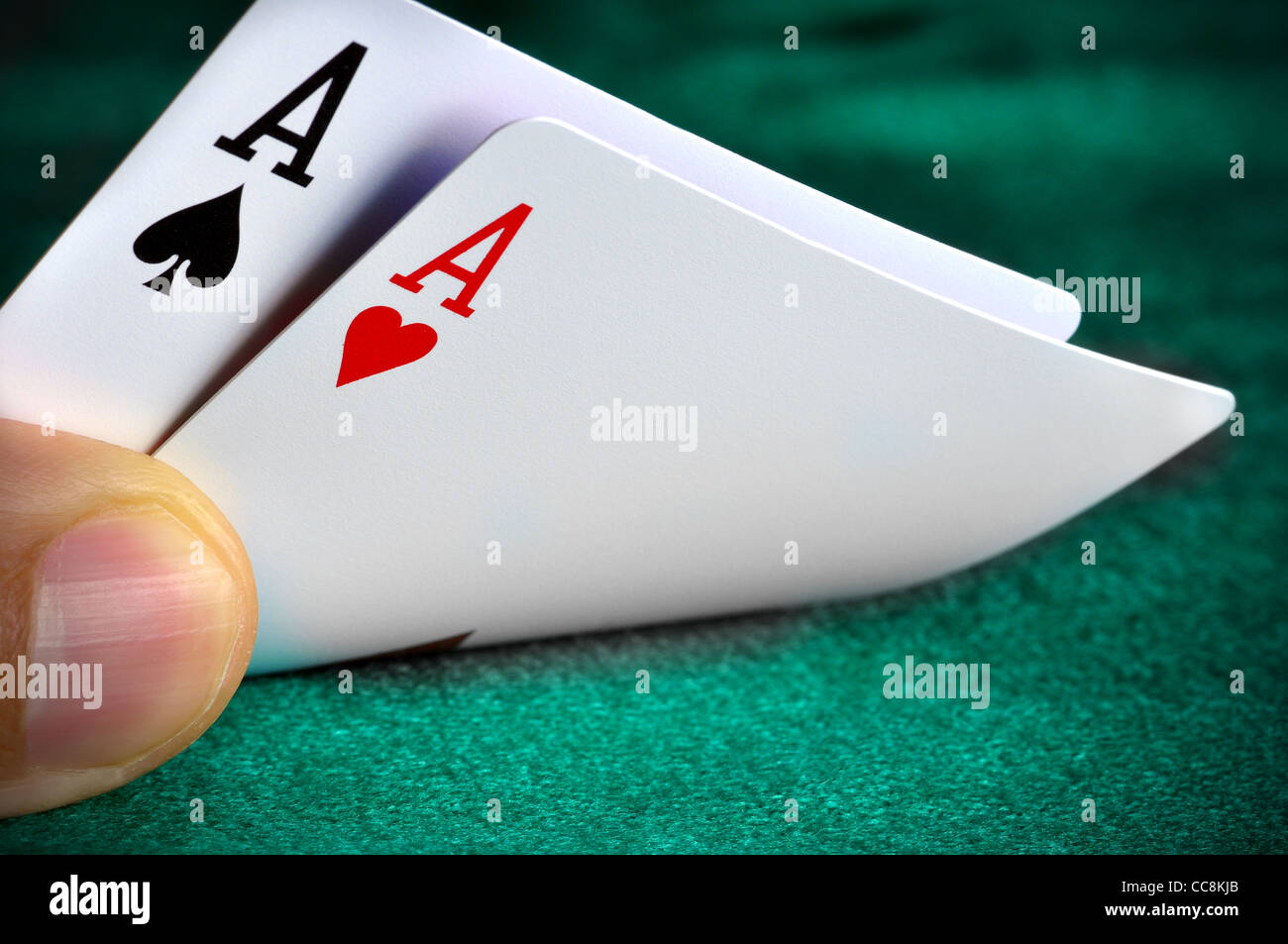 A man playing poker and checking his cards - Stock Image