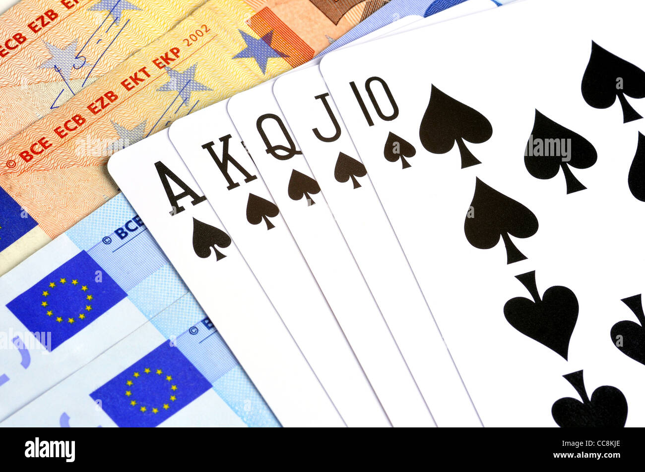 Royal Flush poker hand on top of bank notes - Stock Image