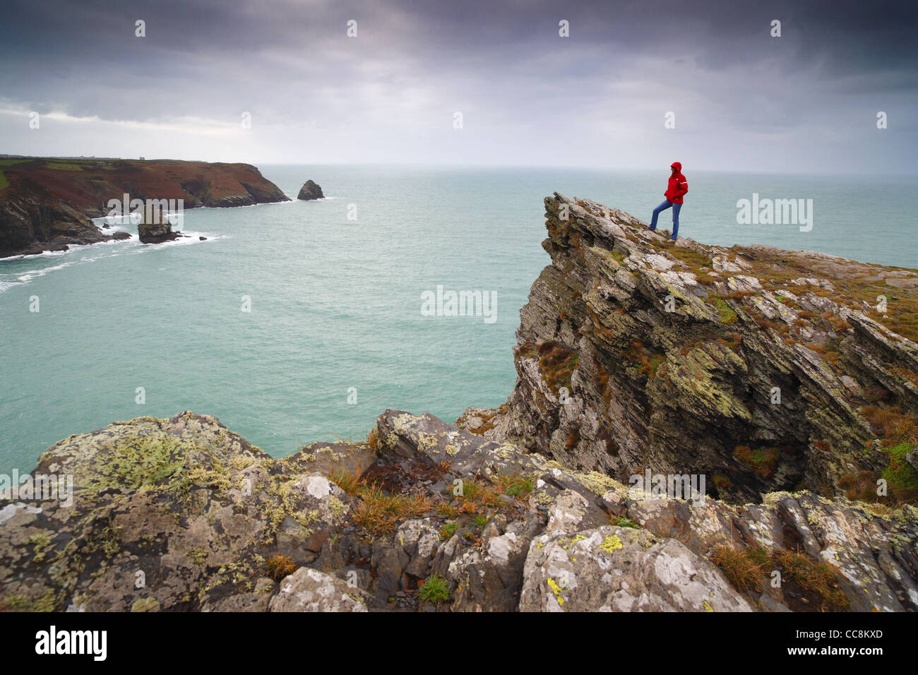 A walker stood on the headland at Boscastle in Cornwall, UK, looking west down the coast towards Tintagel. - Stock Image