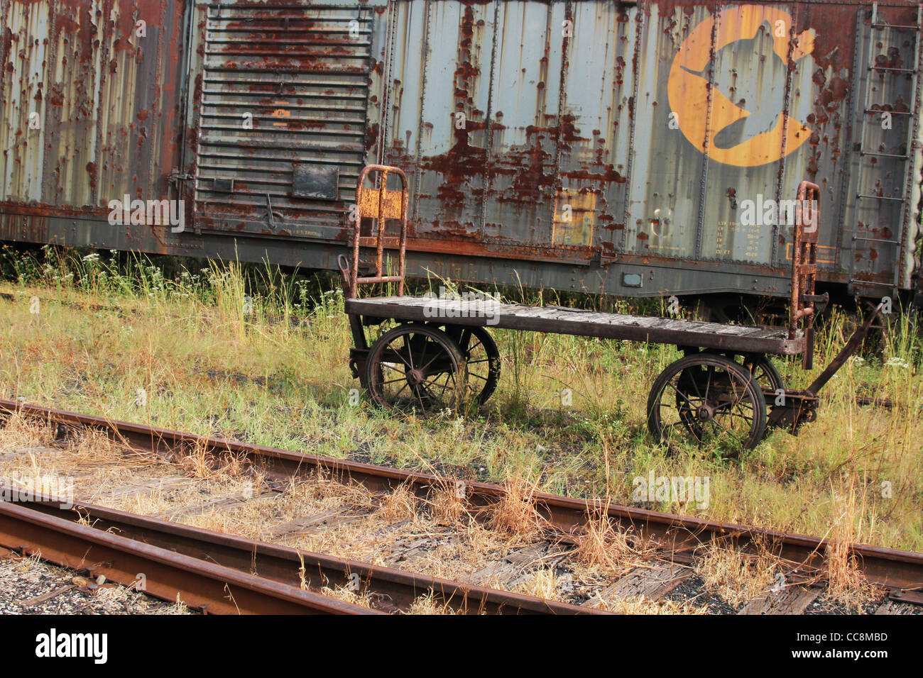 Baggage cart and freight car - Stock Image