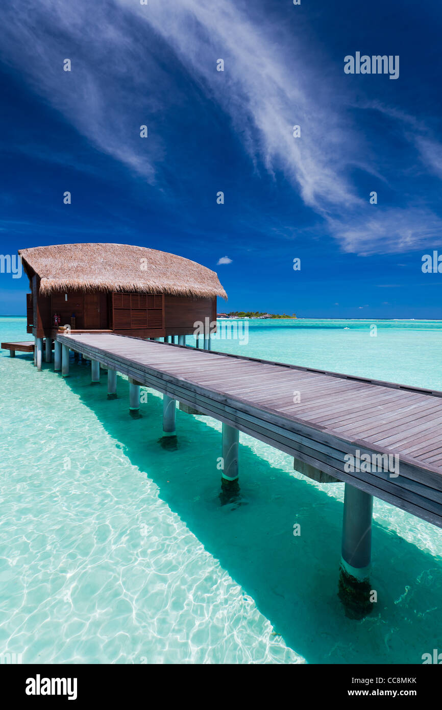 Overwater bungalow in blue lagoon around tropical island - Stock Image