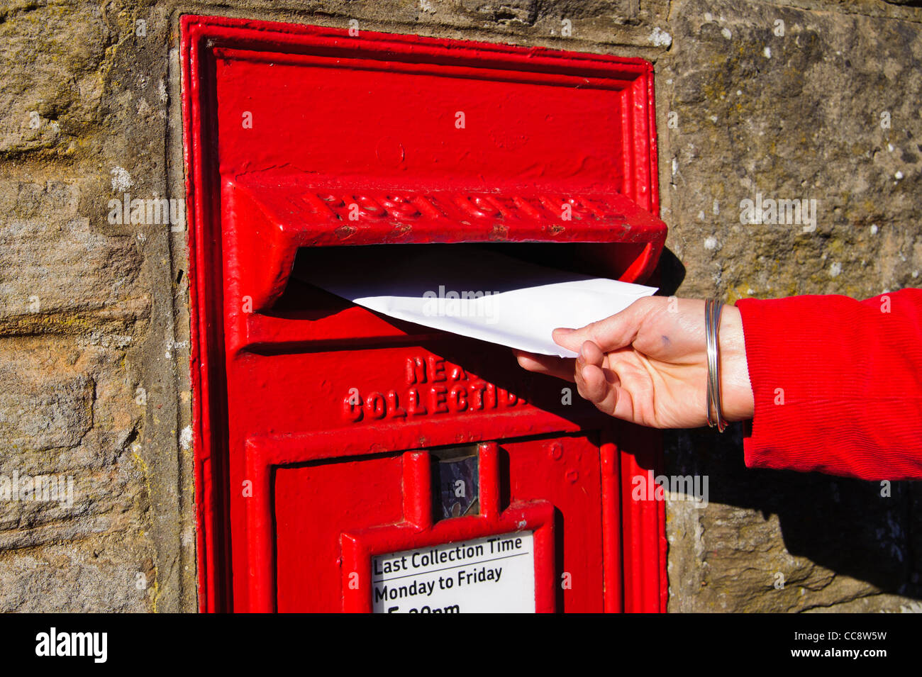 Close up of a hand introducing a letter in a Traditional Royal Mail Letter Box in wall of Edinburgh, Scotland, UK - Stock Image