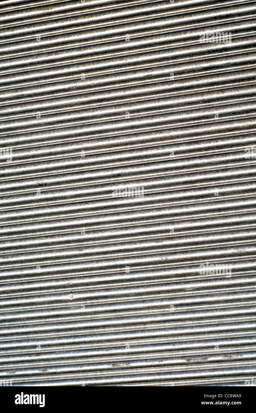 Detail of closed metal shutters on a shop front in the UK highlighting the impact of the recession and economic - Stock Image