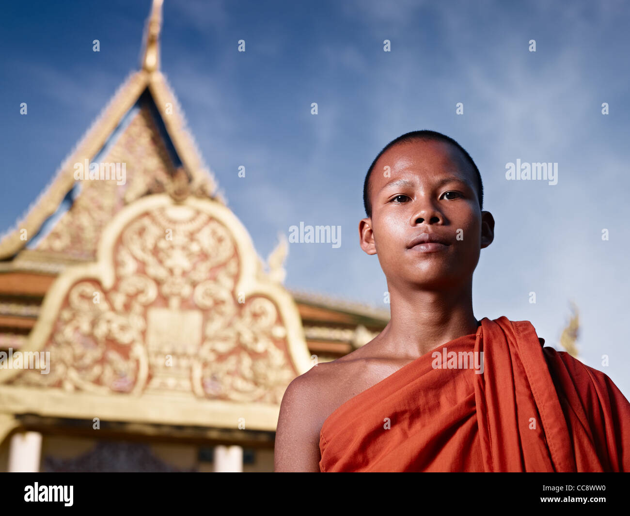 Young Asian monk smiling at camera in buddhist monastery, Phnom Penh, Cambodia, Asia. Low angle Stock Photo