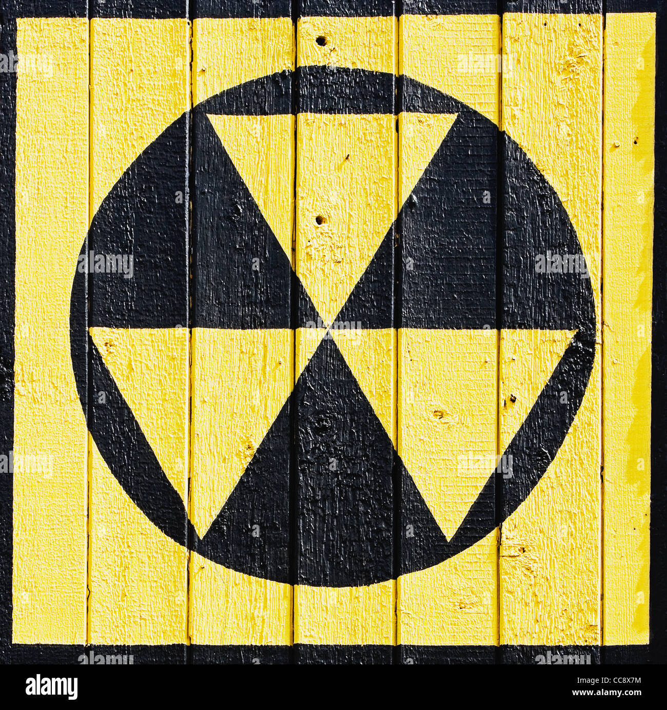 radiation symbol painted on wooden wall - Stock Image