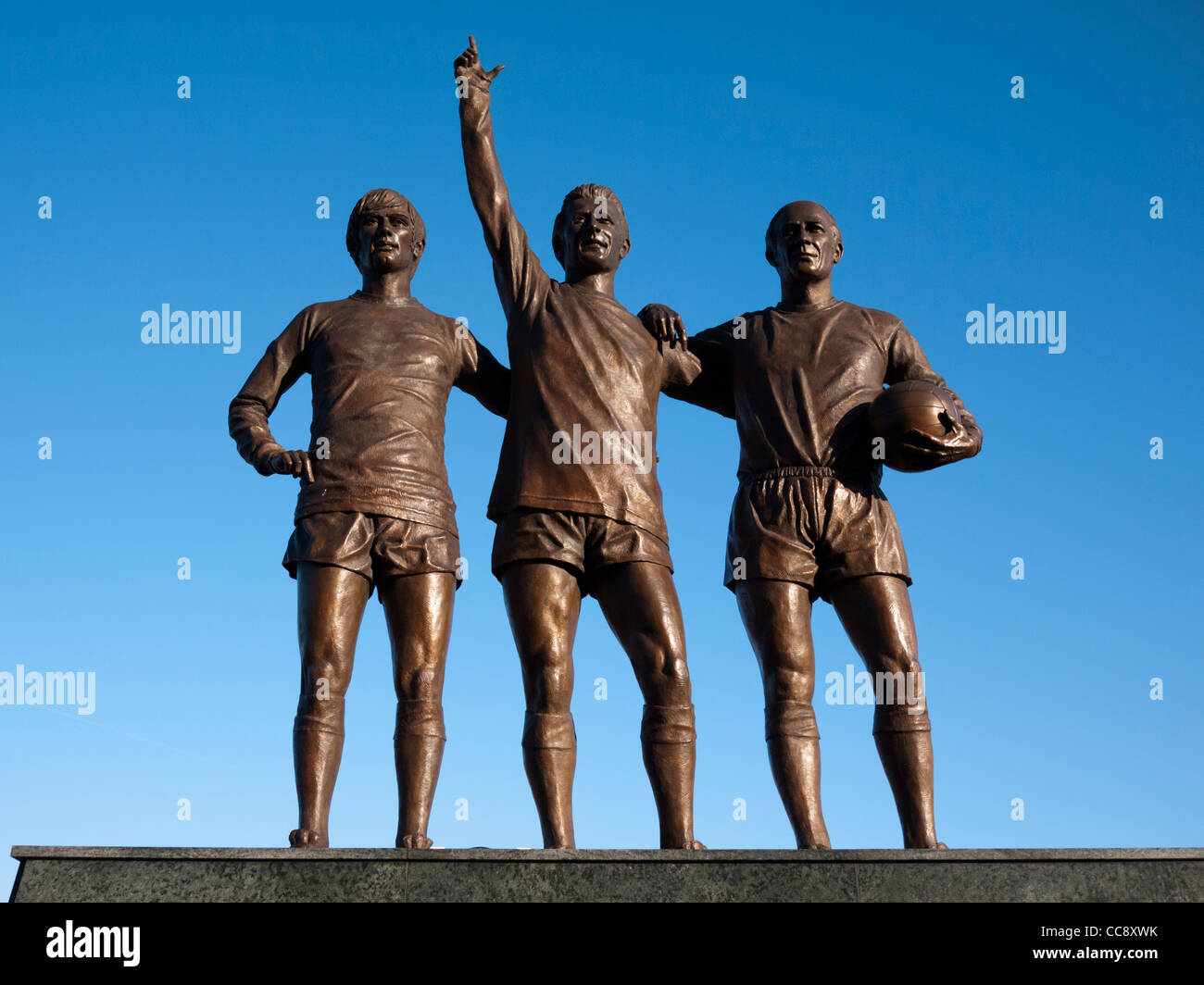 Statues of Sir Bobby Charlton, George Best and Denis Law statue at Old Trafford, Manchester United football ground - Stock Image