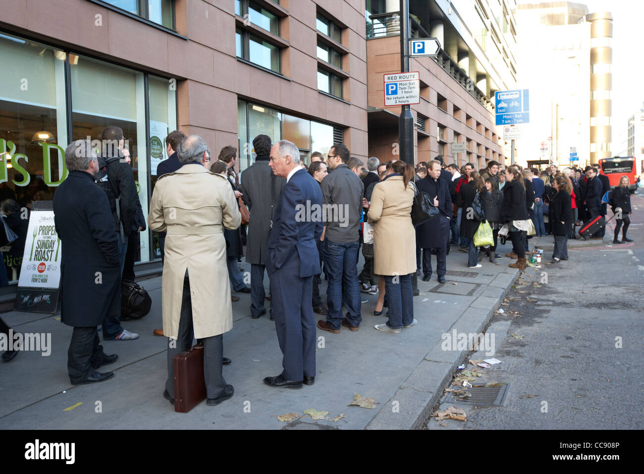 crowd of businesspeople on the street outside an office block as a result of a fire alarm London England UK United Stock Photo