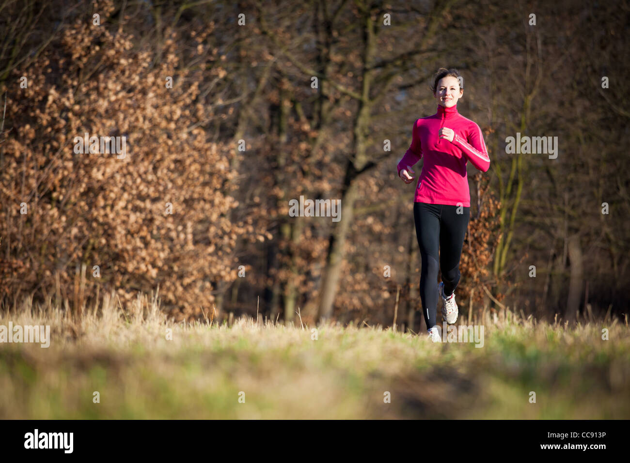 Young woman running outdoors on a lovely sunny winter/fall day (motion blurred image) - Stock Image