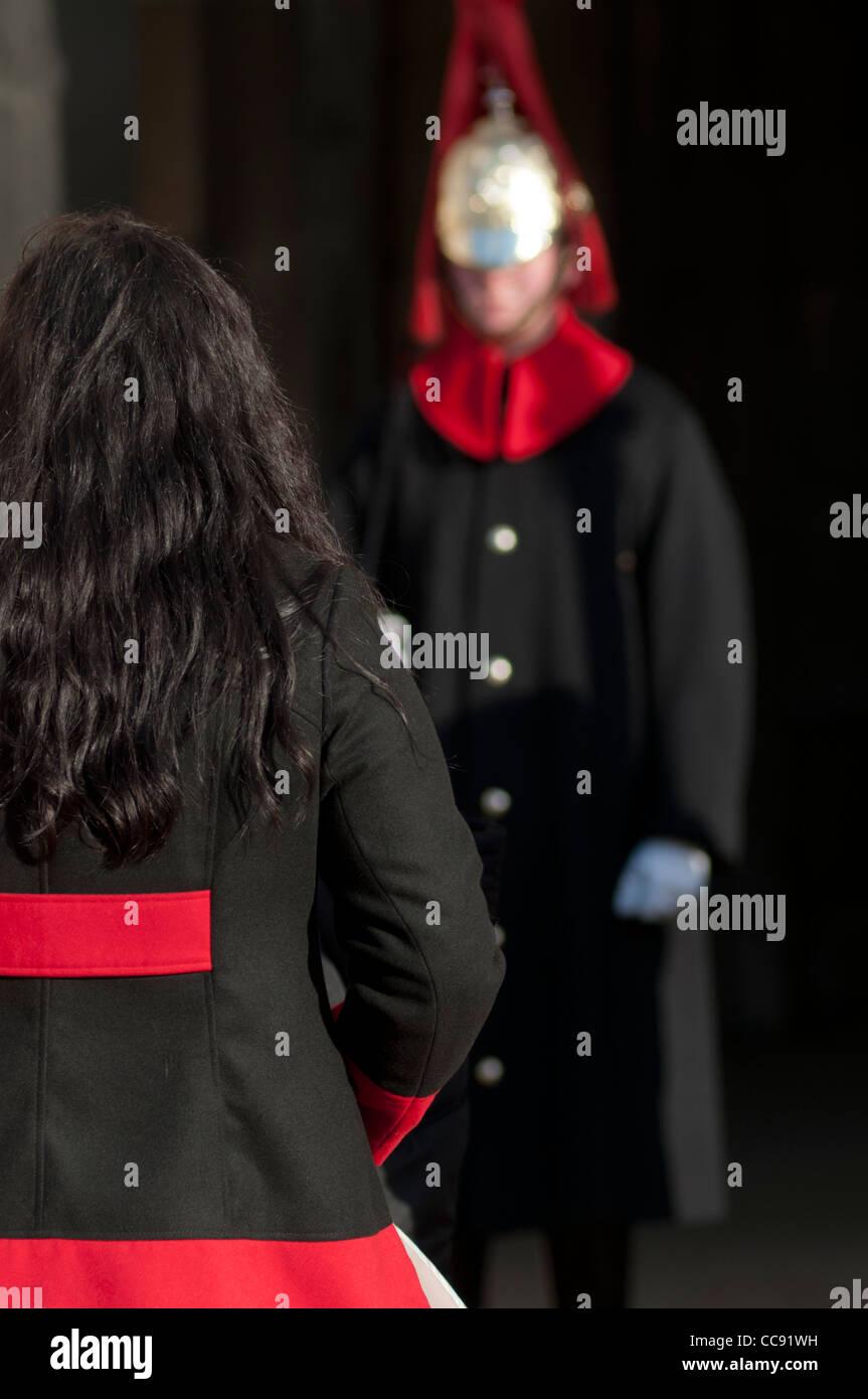 Matching coats of a tourist and Horse Guard at Horse Guards Parade, London, England, UK - Stock Image