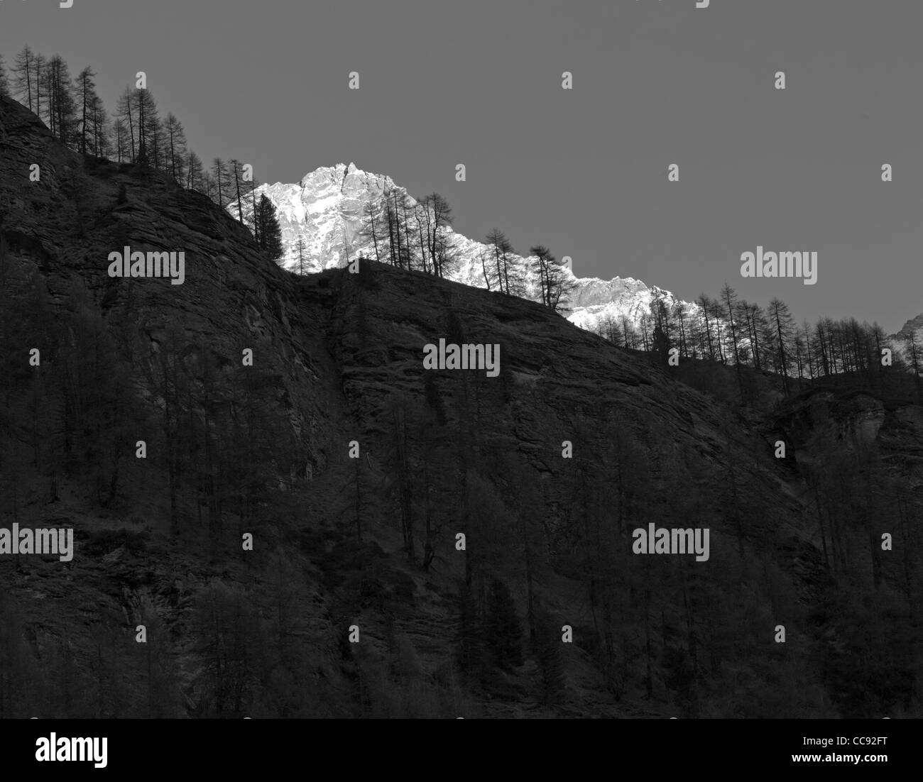 alpenglow reddish glow of a high mountain at sunset near Zinal in black and white - Stock Image