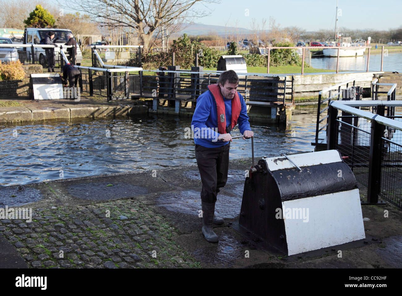 Lock keeper winds open the lock gates at Glasson Dock north west England UK - Stock Image