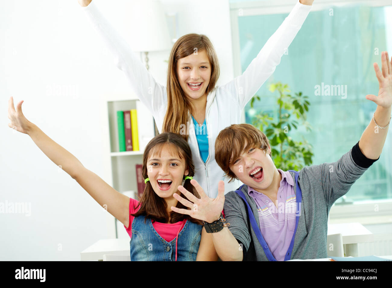 Portrait of smart classmates showing their gladness - Stock Image