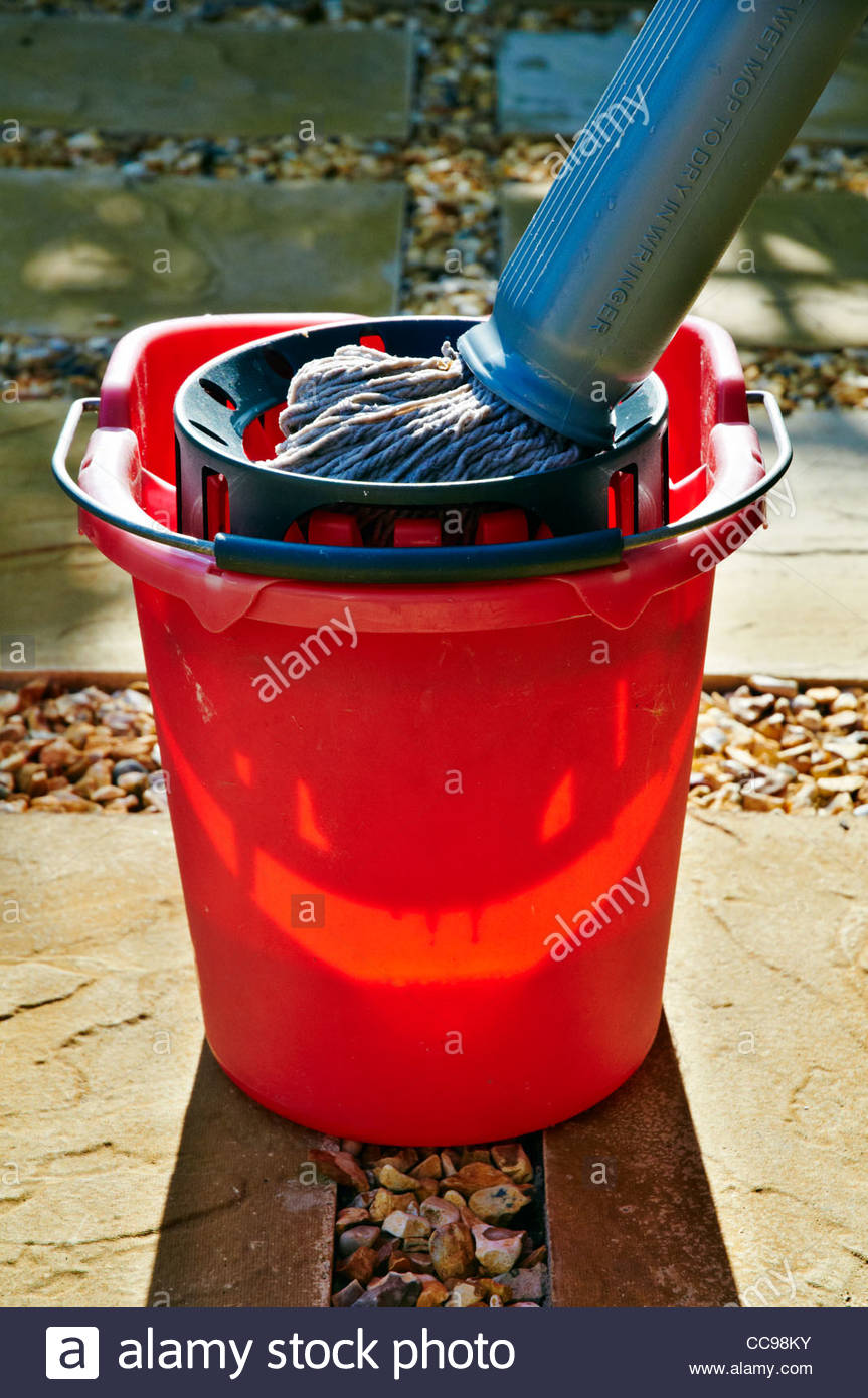 red plastic bucket and floor mop outside in the sunshine - Stock Image
