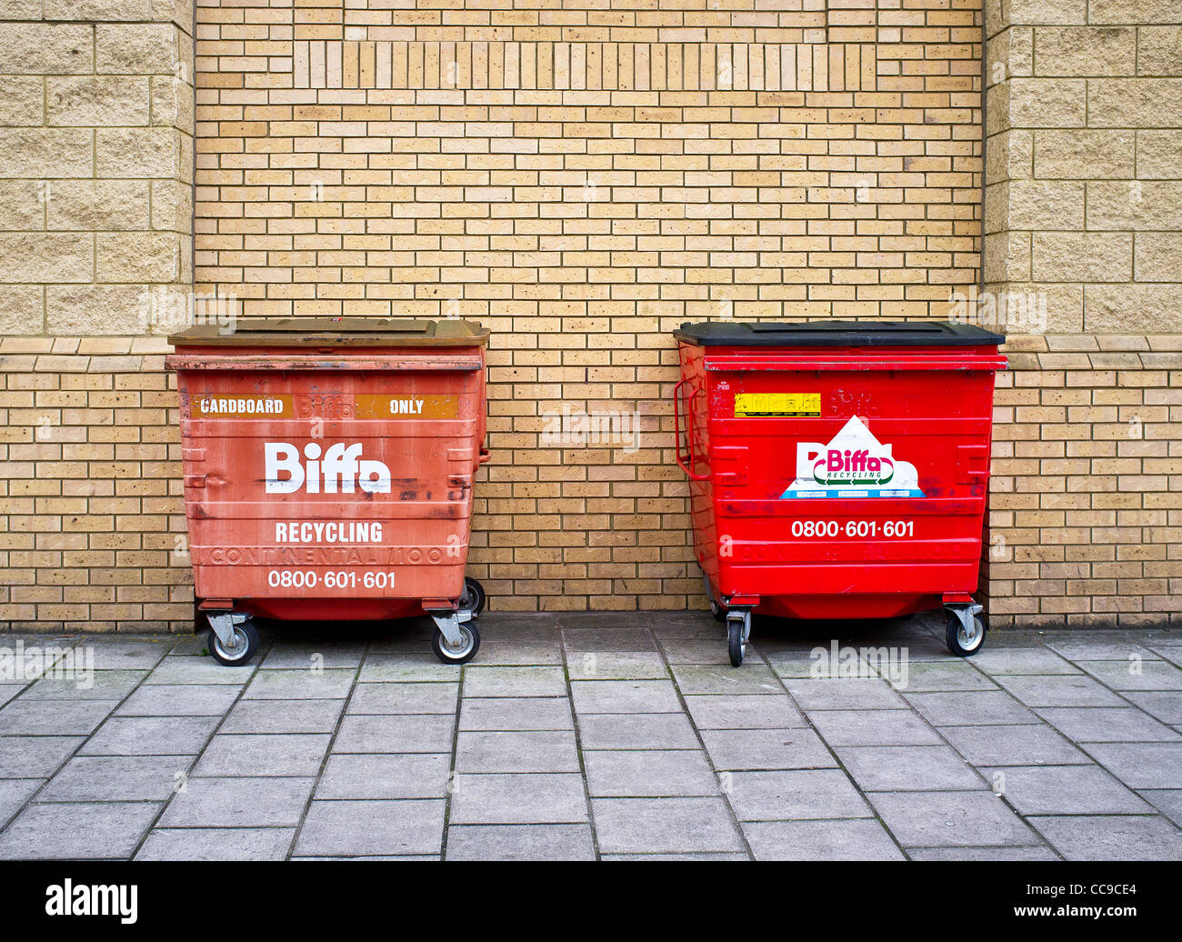 Two recycling bins against a brick wall Stock Photo