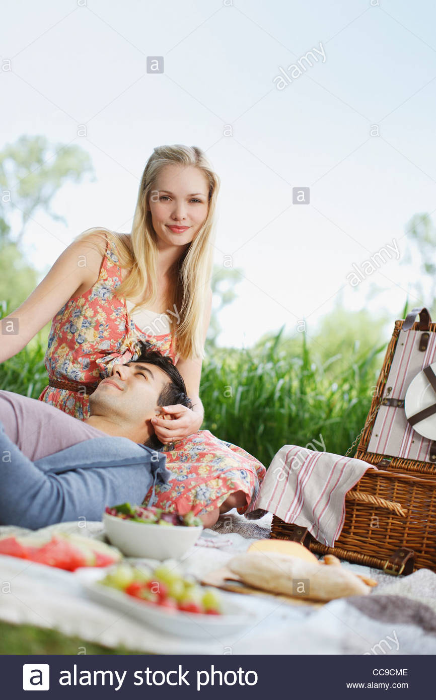 Young couple enjoying picnic in park - Stock Image