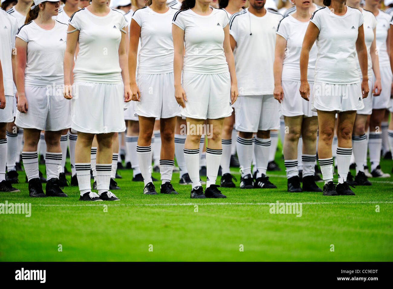 group of teenagers dressed in white during pe-match show of football match - Stock Image