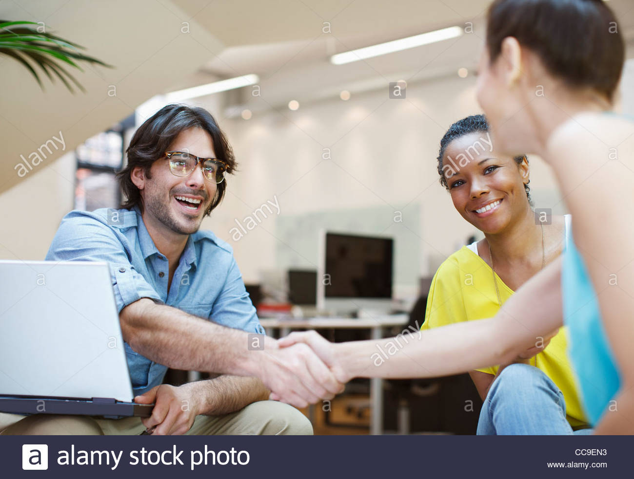 Businessman and businesswoman handshaking in meeting - Stock Image