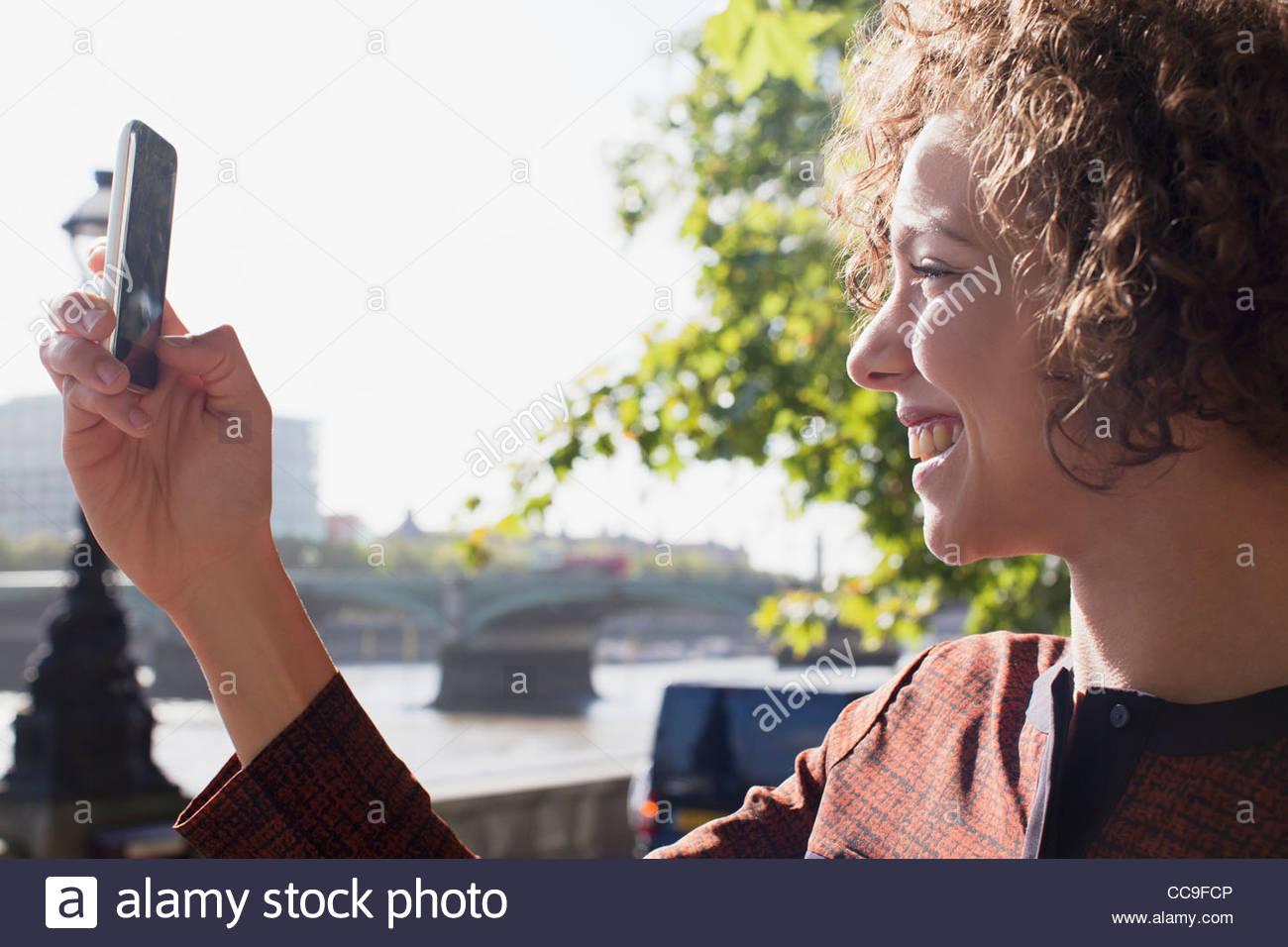 Close up of smiling woman taking photograph with camera phone - Stock Image