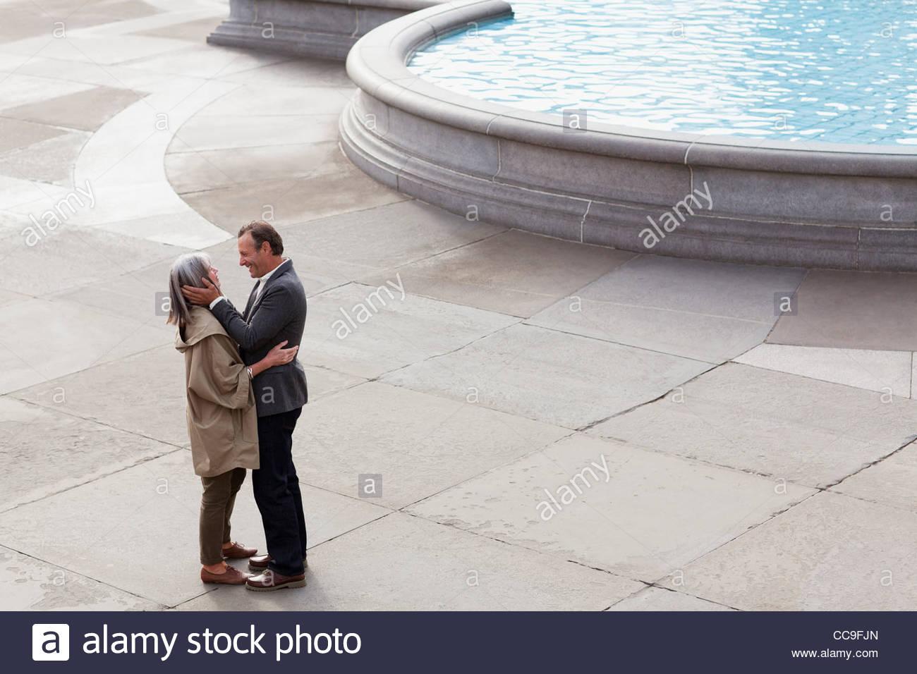 Couple hugging face to face near urban fountain - Stock Image