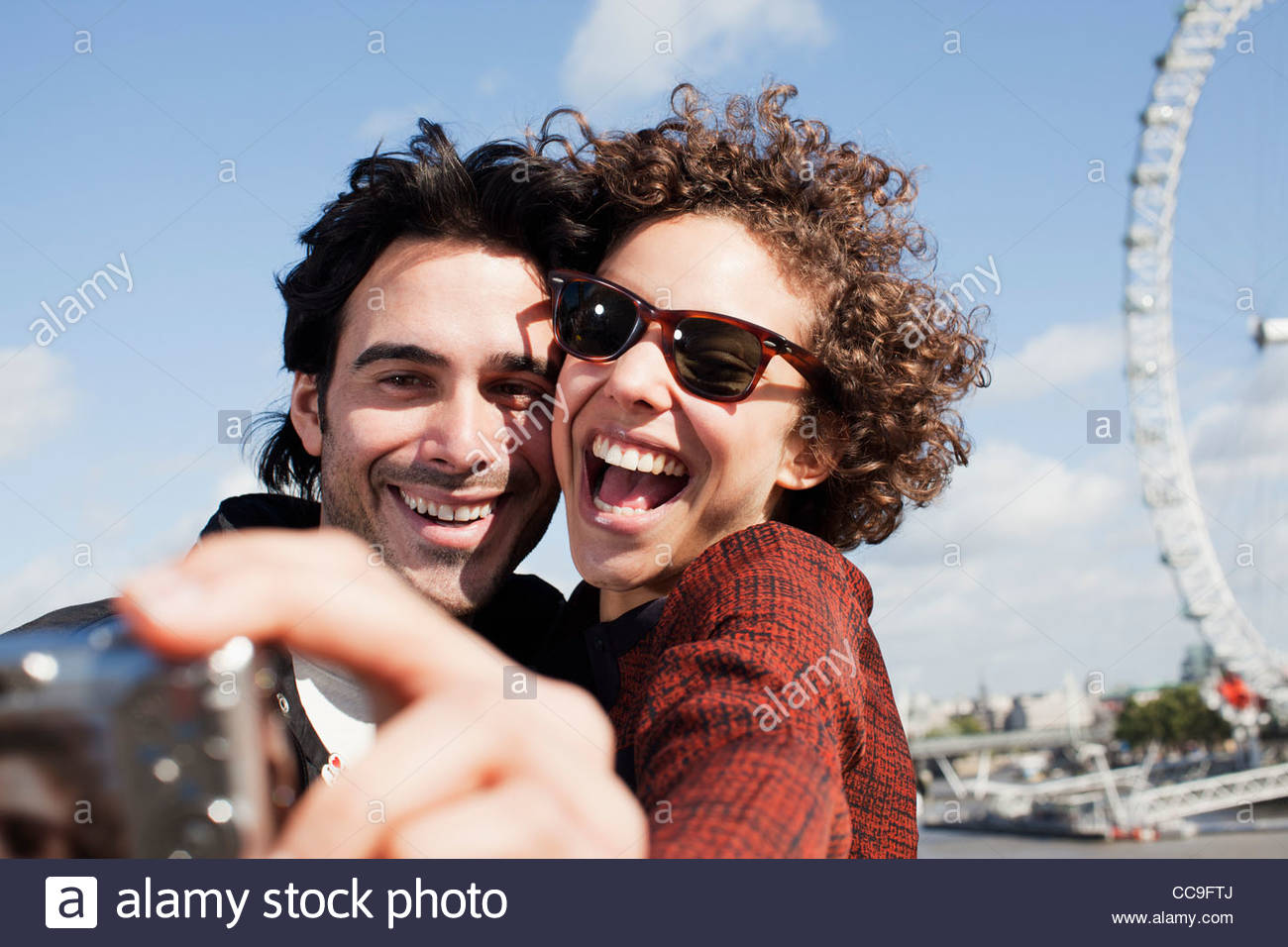 Happy couple taking self-portrait with digital camera near London Eye - Stock Image