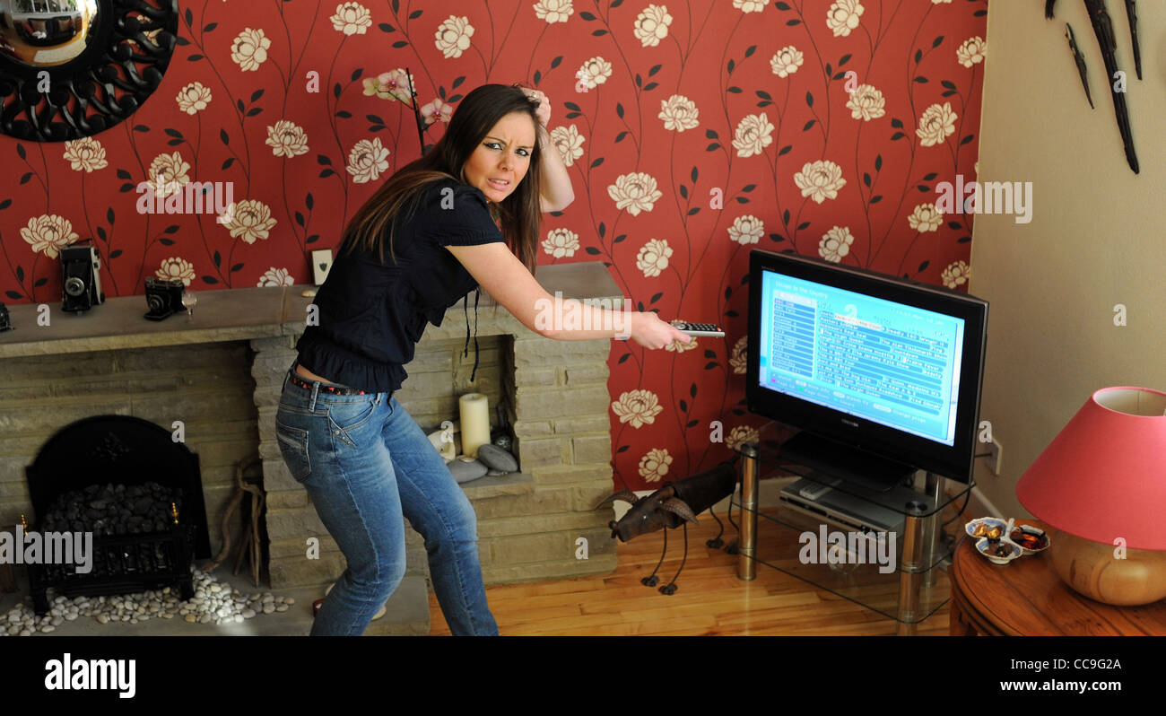 Young woman having trouble with the Digital Television Switchover in the UK phones a helpline - Stock Image
