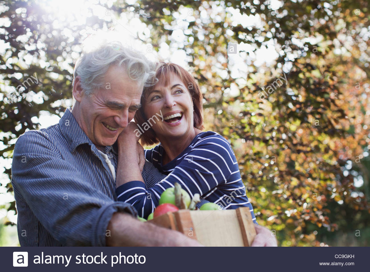 Happy senior couple with bushel of apples hugging - Stock Image