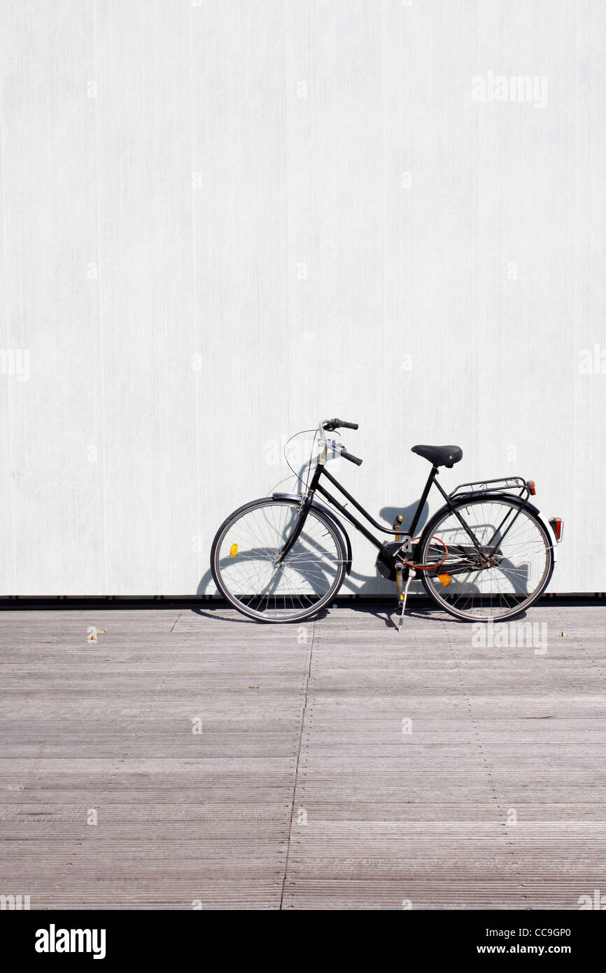 A bike leaning on a wall - Stock Image