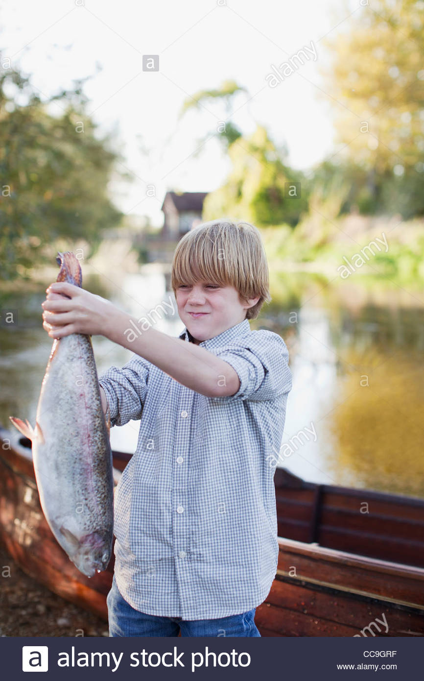 Boy making a face and holding fish in front of lake - Stock Image