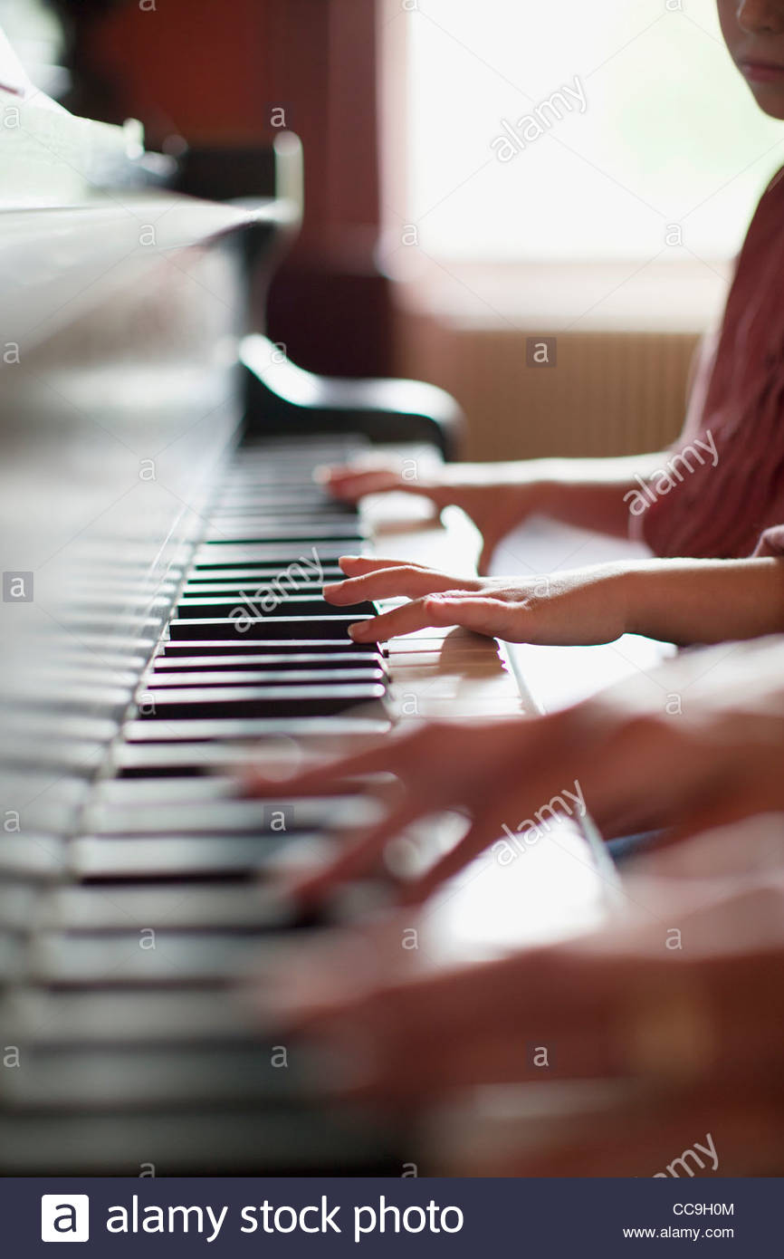 Close up of hands on piano - Stock Image