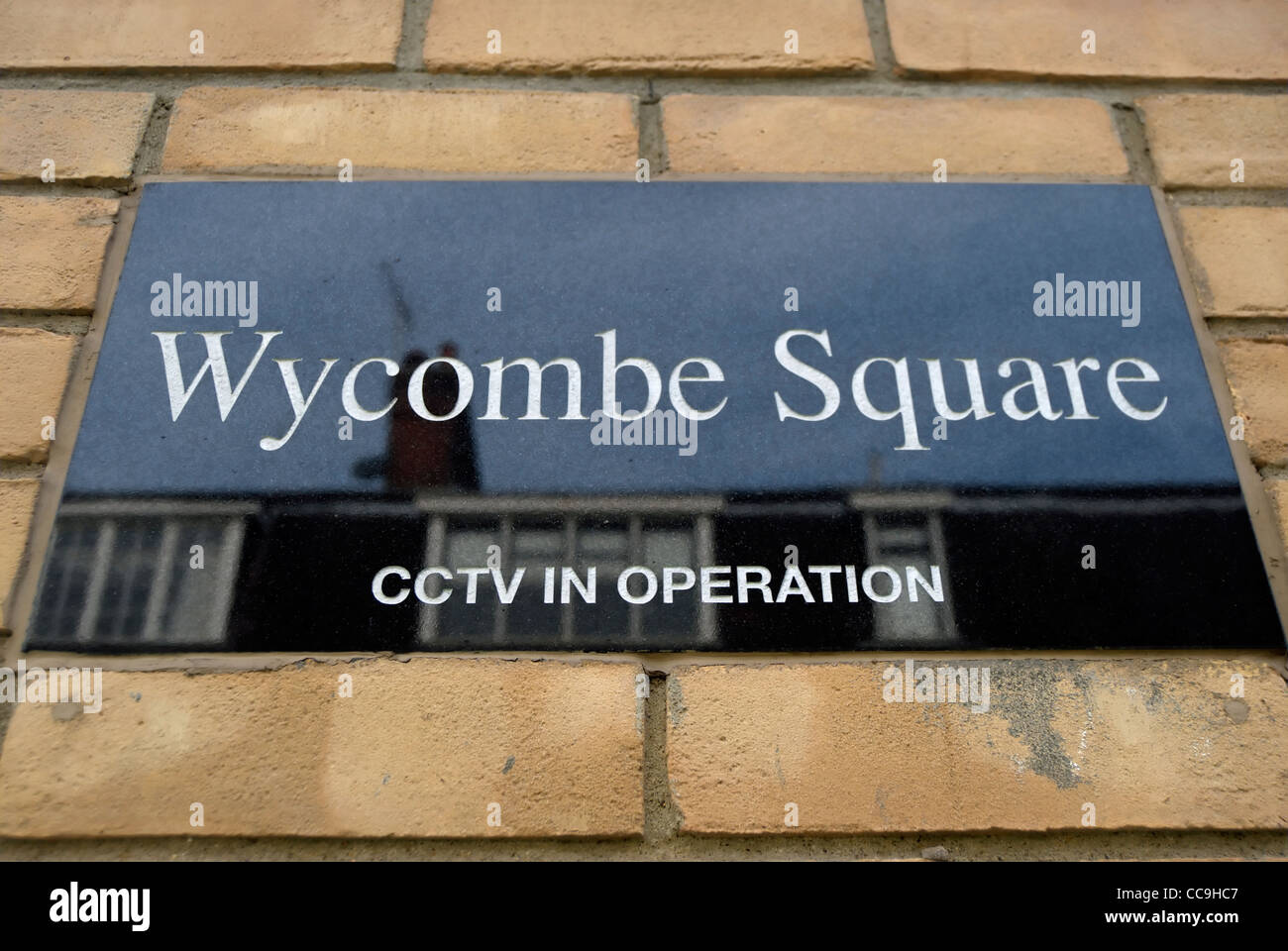 street name sign for wycombe square with warning of cctv in operation, notting hill, london, england - Stock Image
