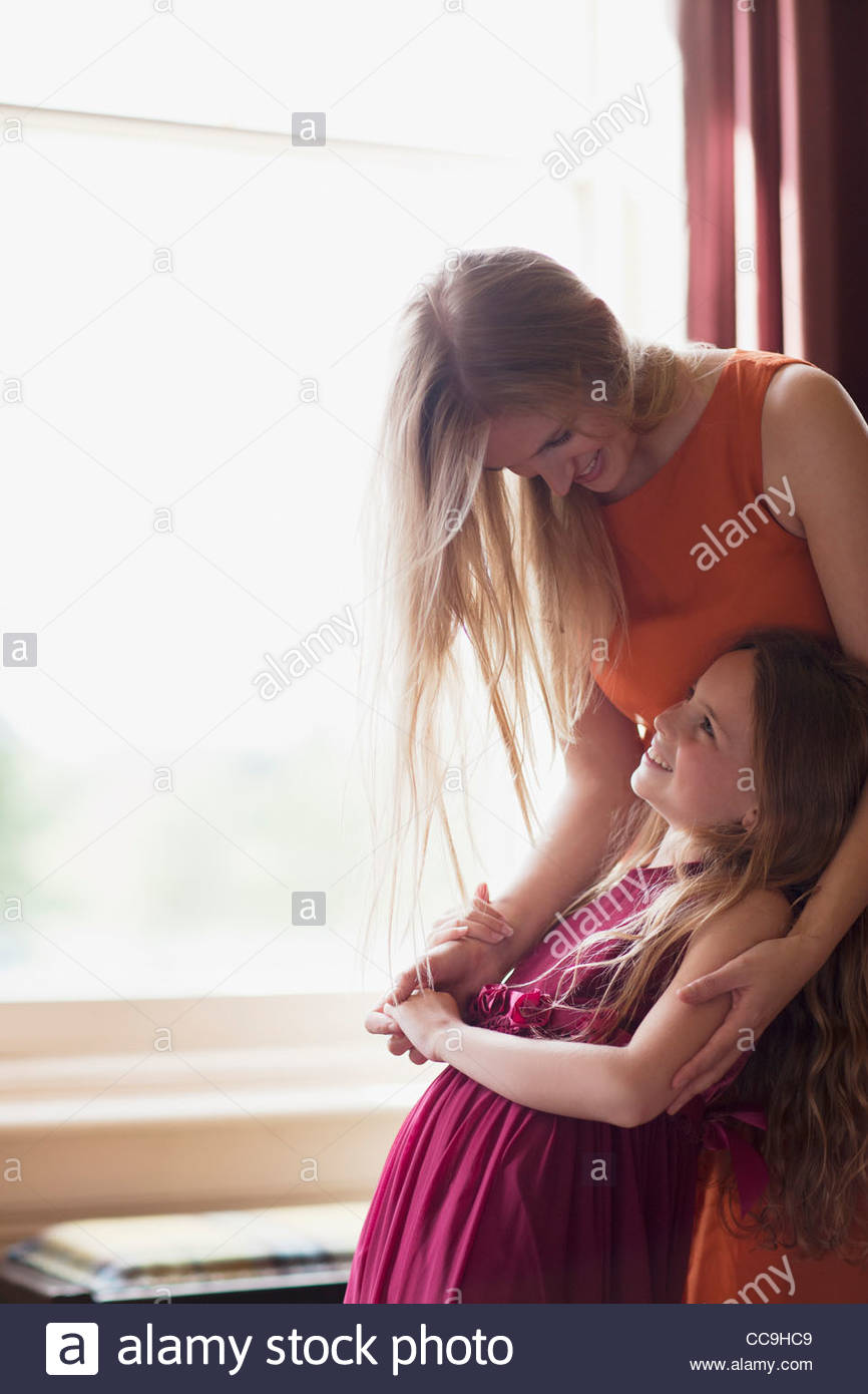 Sisters hugging near window - Stock Image
