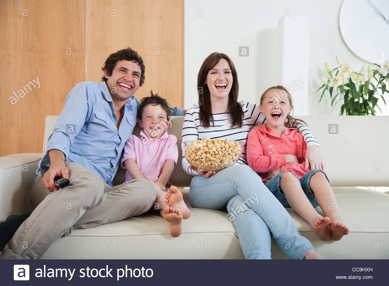 Laughing Family Watching TV On Sofa