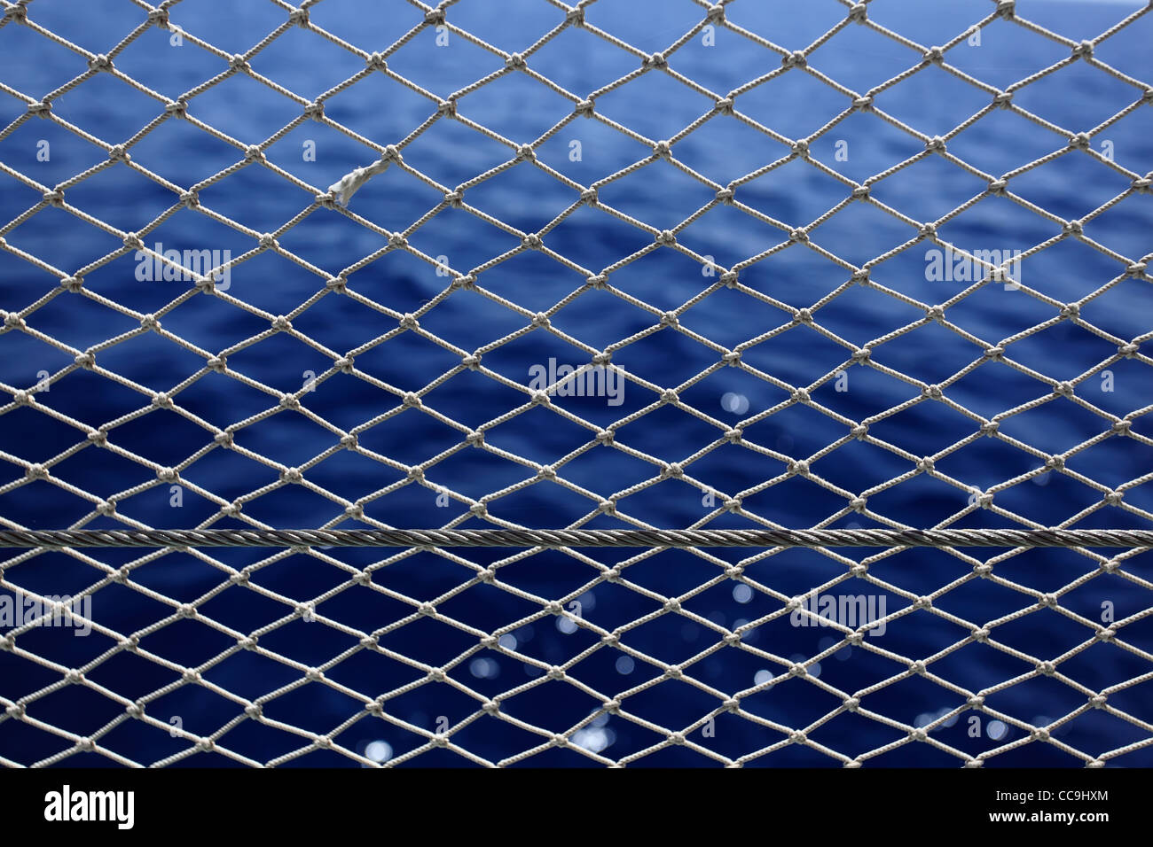 Net with deep blue sea on a background. - Stock Image