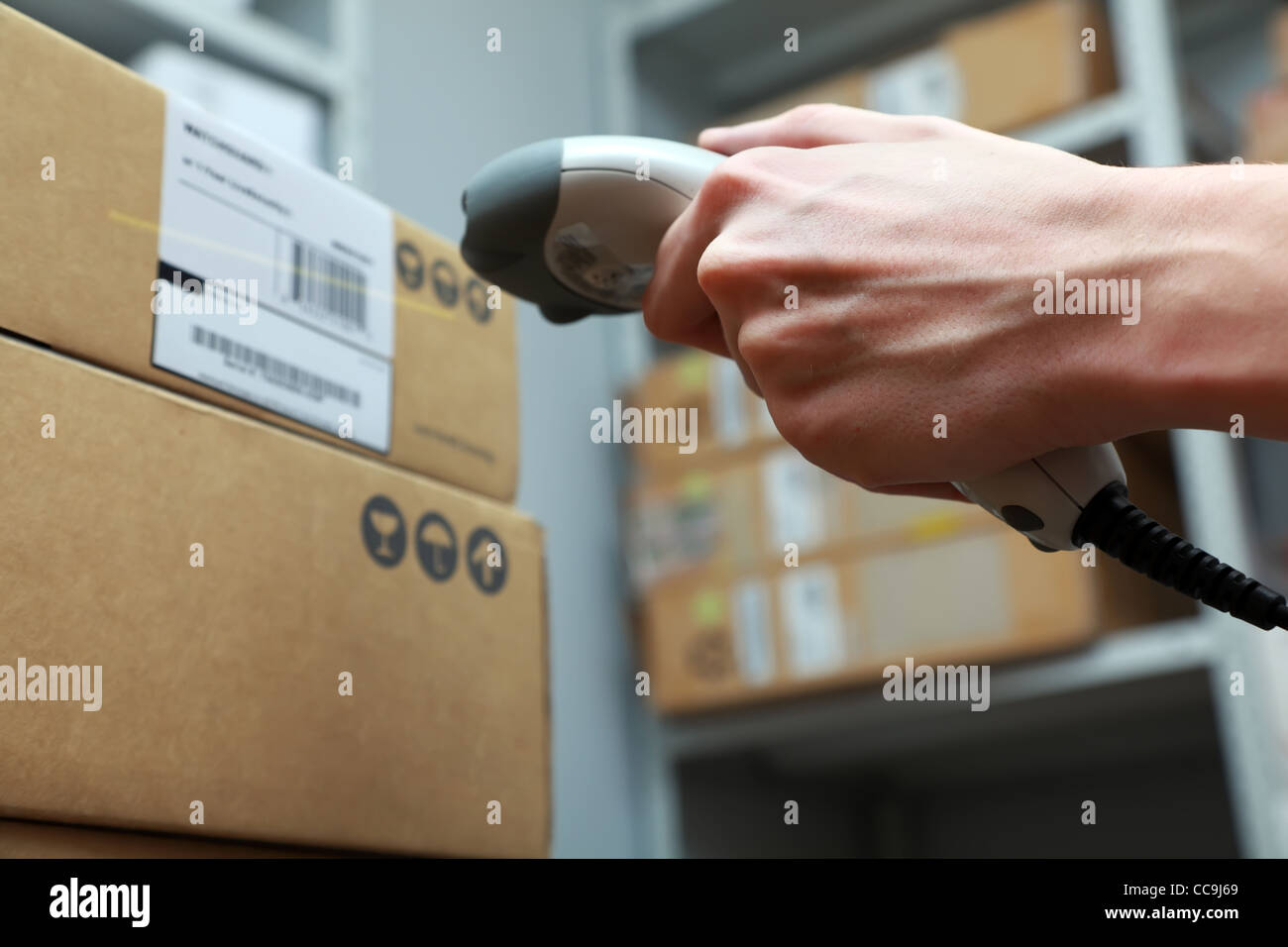 Warehouse works. Man hand hold barcode scanner. - Stock Image