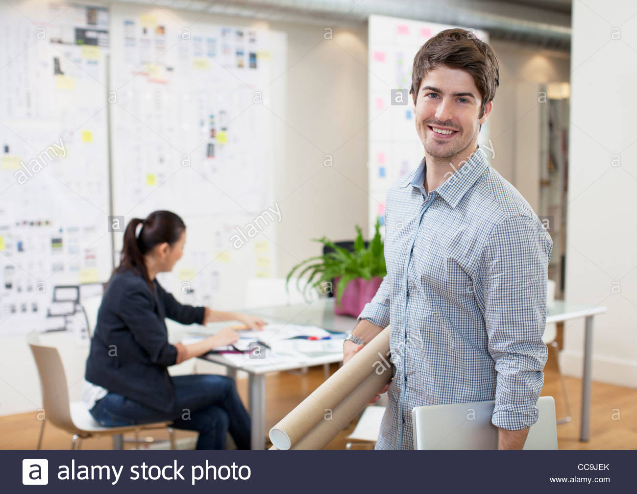 Portrait of smiling architect holding blueprint tubes in office portrait of smiling architect holding blueprint tubes in office malvernweather Image collections