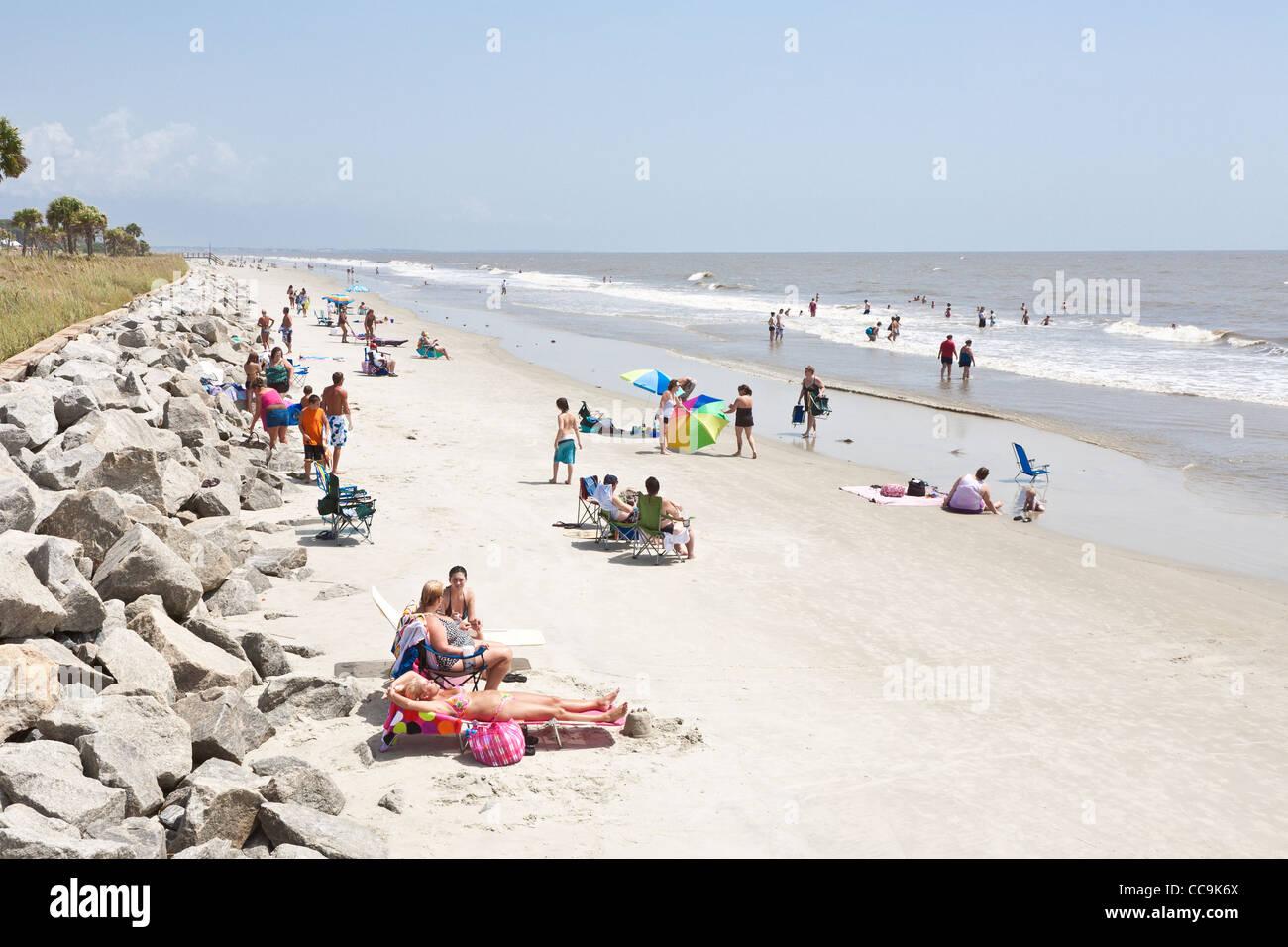 Sunbathers and colorful beach umbrellas on the public beach at Jekyll Island, Georgia. - Stock Image