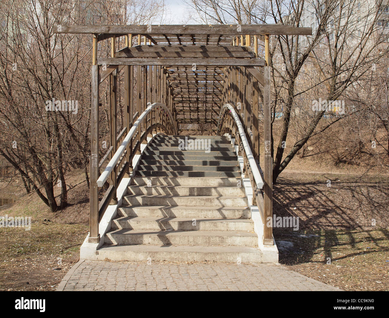 The humpbacked bridge thrown through small river in old park. - Stock Image