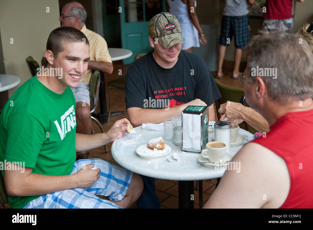 Family eating beignets and drinking coffee at table in Cafe Du Monde in the French Quarter of New Orleans, LA - Stock Image