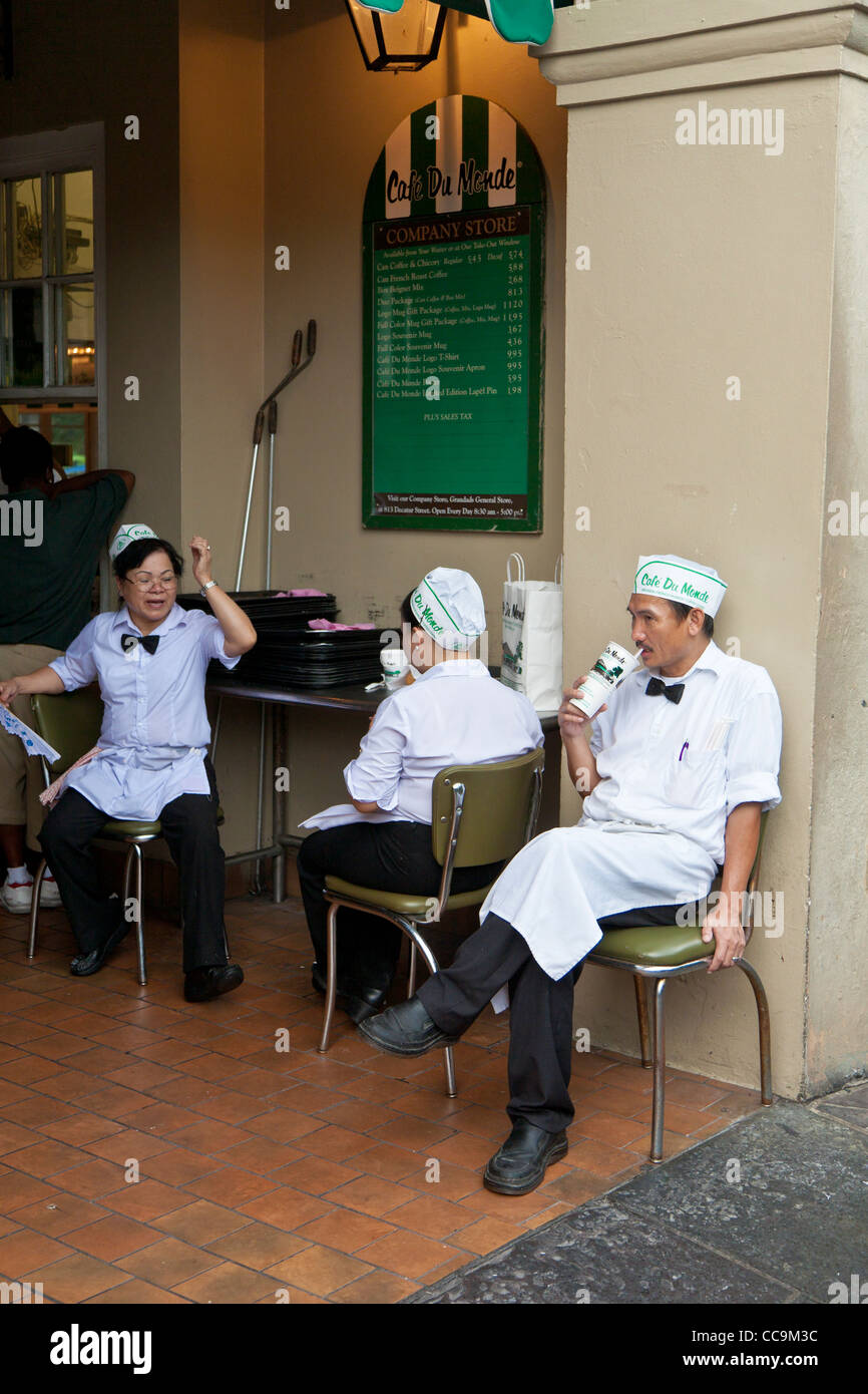 Employees take a break from serving beignets and coffee at Cafe Du Monde in the French Quarter of New Orleans, LA - Stock Image