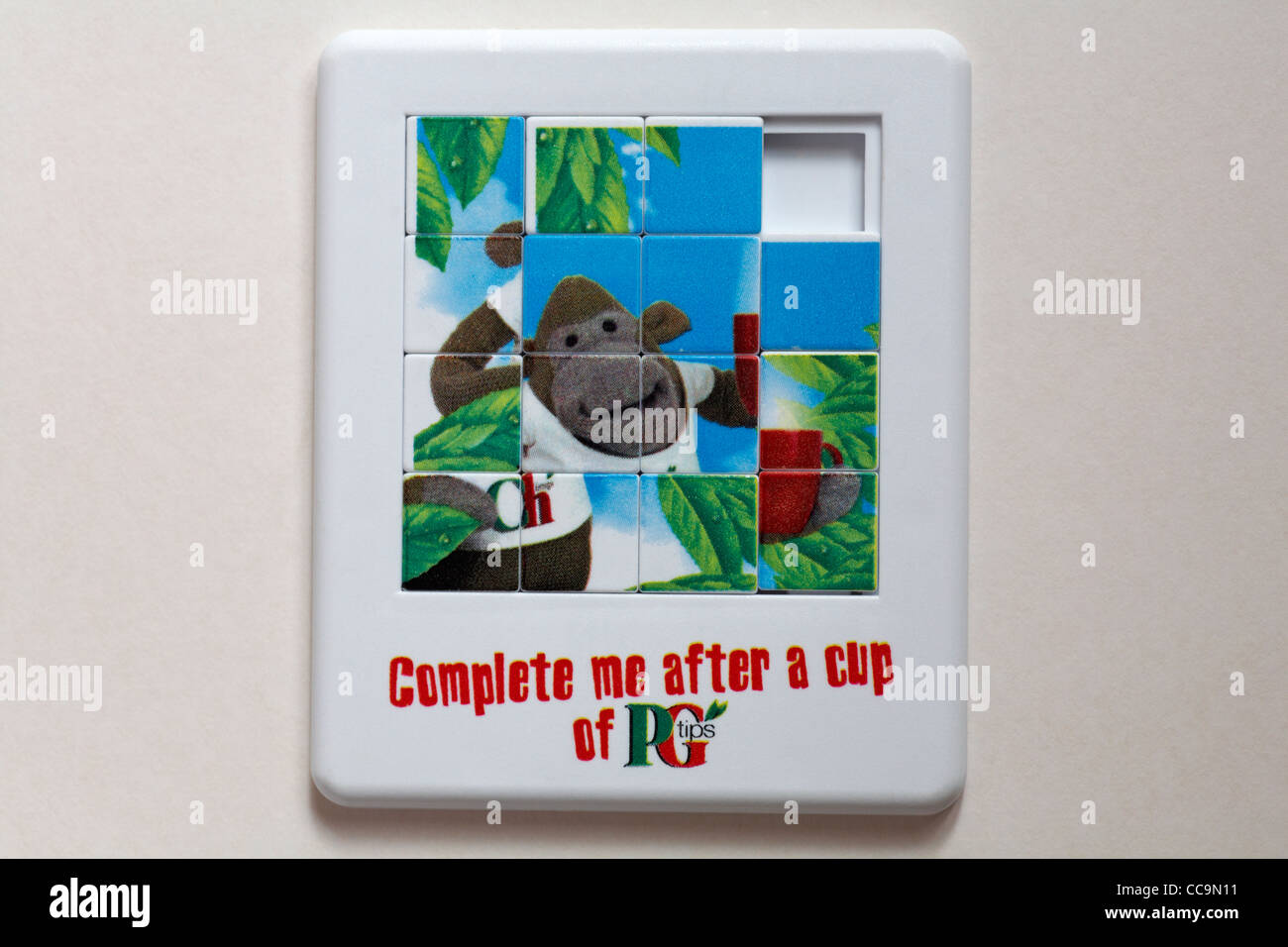 Complete me after a cup of PG Tips tea slide puzzle isolated on white background - Stock Image