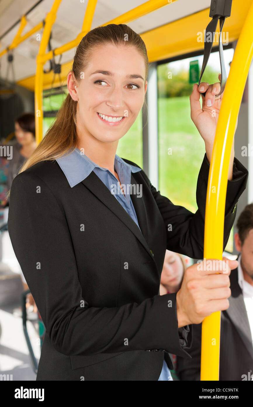 Female passenger in a bus; presumably she is heading home - Stock Image