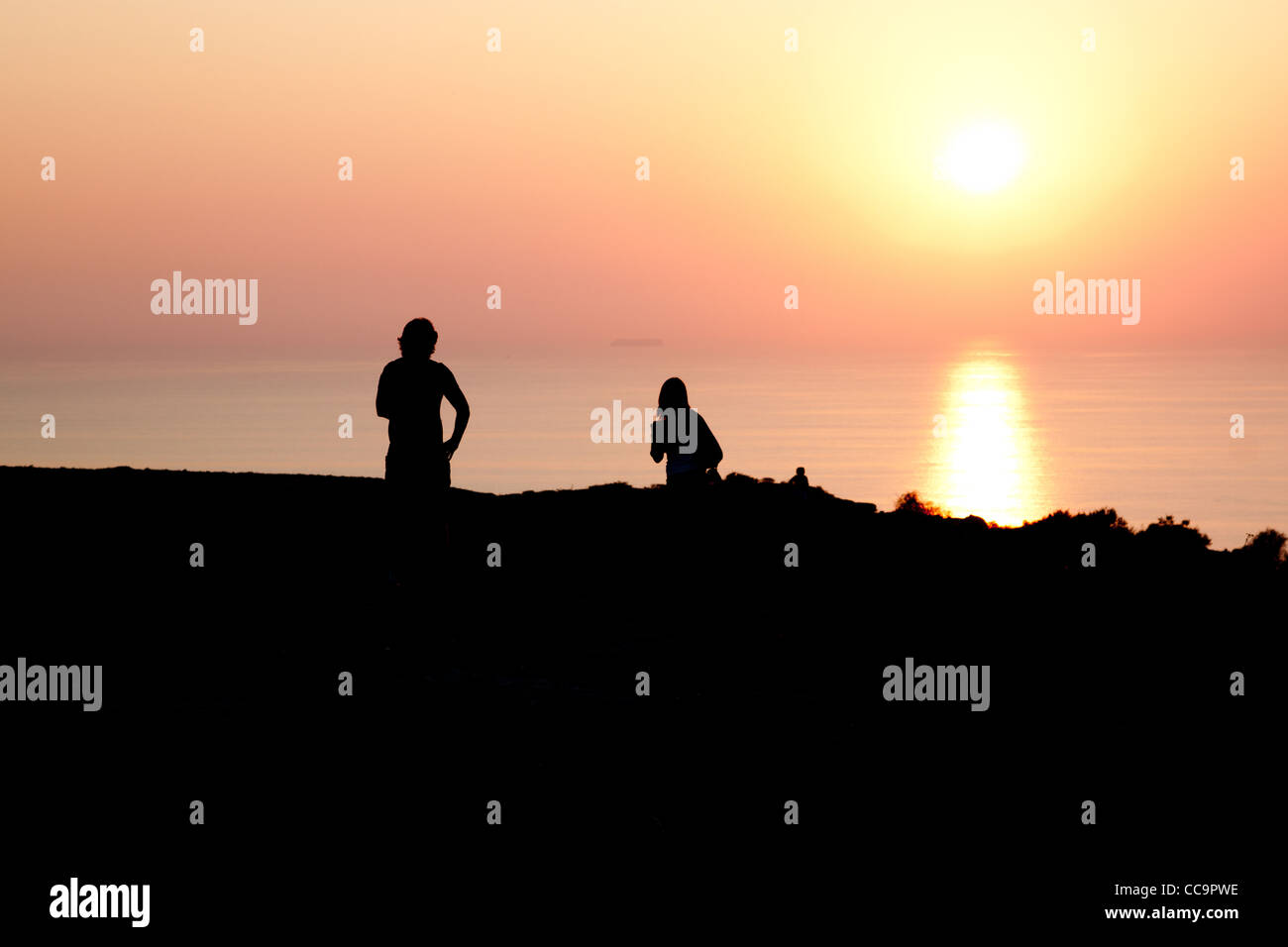 Two People Silouettes on Sunset in Lampedusa - Stock Image