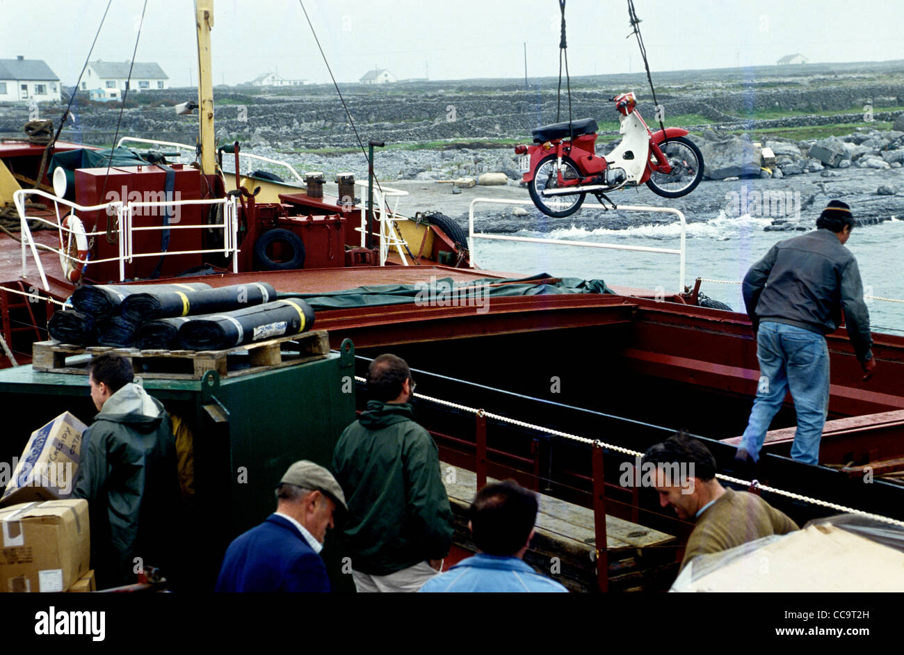 A motor cycle is craned ashore on the Aran Islands Co Galway Ireland - Stock Image
