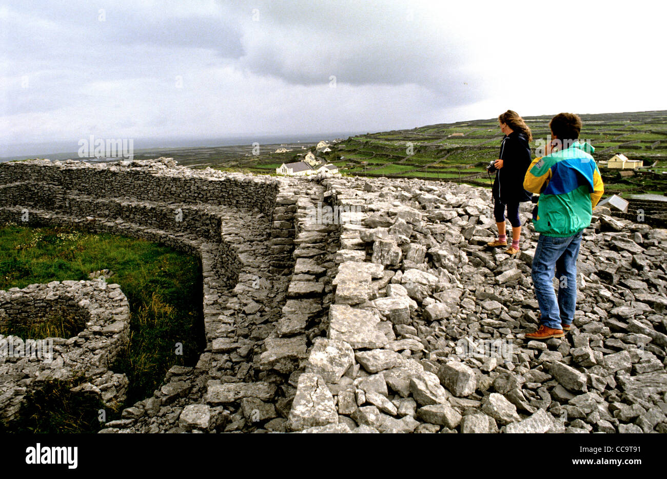 Two visitors explore one of a number of Iron Age forts on the Aran Islands. This one is in Inis Oirr - Stock Image