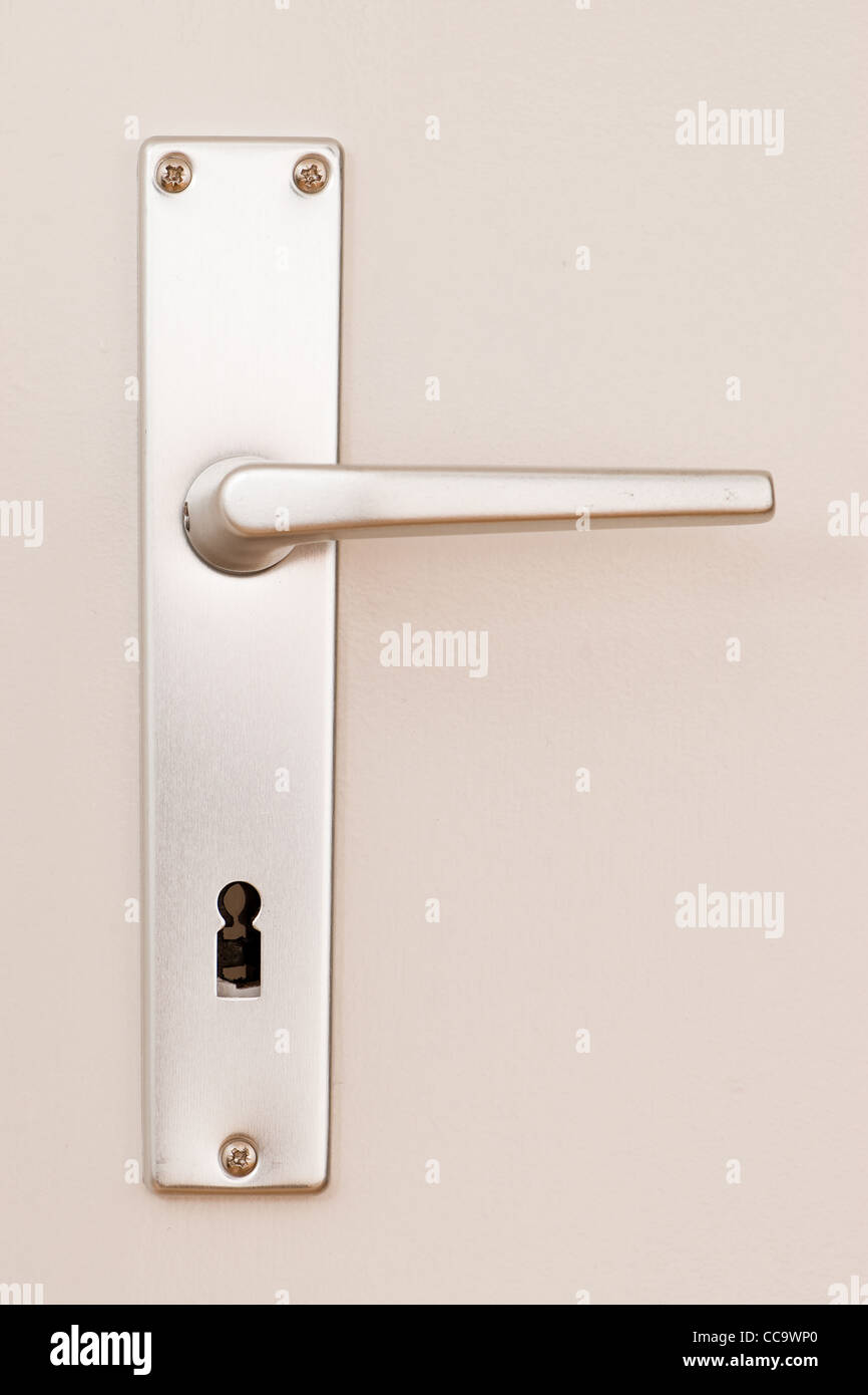 frontal view of a clean metal doorhandle on a bright painted door - Stock Image