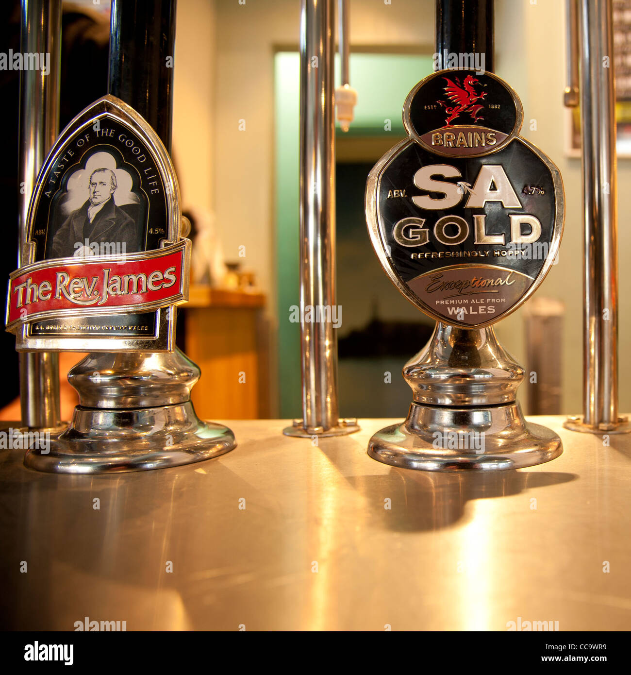Cardiff brewery Brains SA Gold and The Rev James draught beer pumps in a pub bar UK Stock Photo
